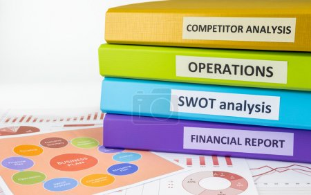 Photo for Colorful document binders: SWOT, competitor analysis, operation and financial report place on graph analysis and business plan chart, concept to business plan management - Royalty Free Image