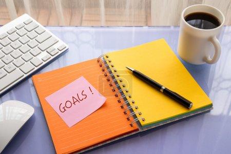 Photo pour Mot de buts sur note pad bâton sur cahier vierge colorée à l'espace de travail, notions de résolution de l'année - image libre de droit