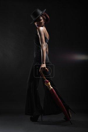 Photo pour Jeune femme avec parapluie à la main sur un fond noir - image libre de droit