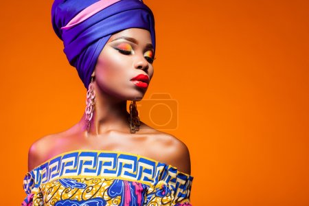 Photo pour Femme africaine dans une robe brillante sur fond orange - image libre de droit