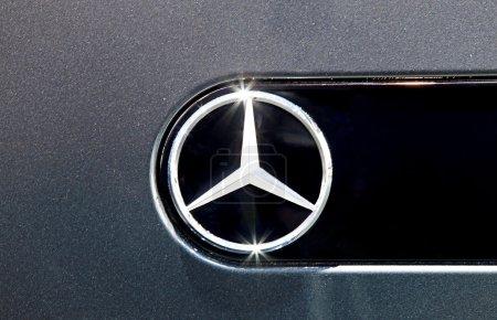 close up logo of Mercedes Benz on black car