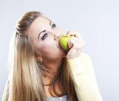 Usměvavá dívka s zelené jablko. Široký úsměv. Zdravé zuby