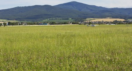 Beautiful mountain landscape with a small plane in the background. Plane by a single pilot. steppe