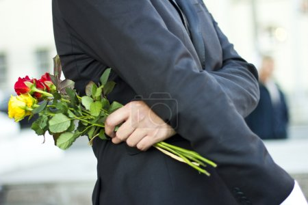 Brutal man in a black suit and white shirt with a bouquet of roses in hands