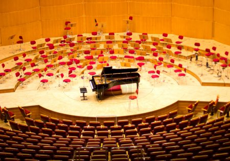 Large black grand piano on a bare stage. Musical instrument.