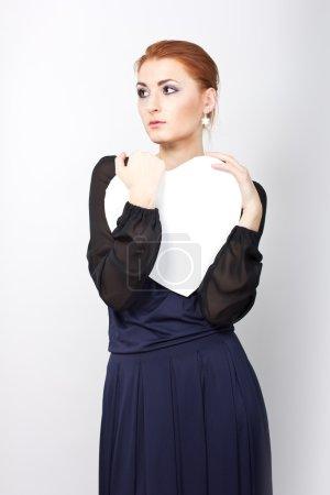 Photo pour Belle fille mince en robe du soir avec un grand coeur blanc. Portrait d'une jeune rousse - image libre de droit