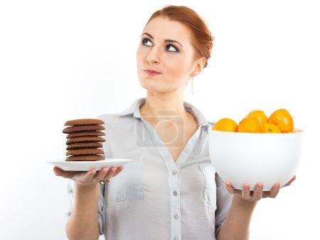 Photo pour Jeune fille mince avec des mandarines et biscuits aux pépites de chocolat. Portrait d'une femme au régime. Savoureux et utile. Compter les calories. Portrait d'une fille isolée sur un blanc - image libre de droit