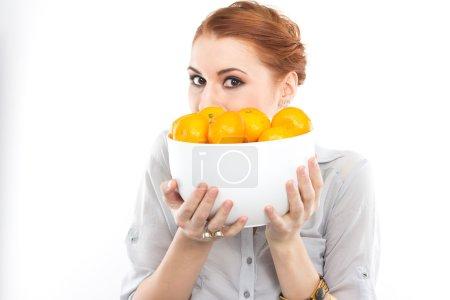 Photo pour Jeune fille mince avec des mandarines. Portrait d'une femme au régime. Savoureux et utile. Compter les calories. Portrait d'une fille isolée sur un blanc - image libre de droit