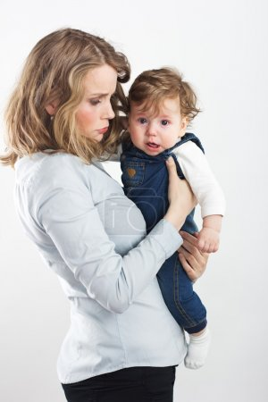 Young mother with a little boy in her arms. Portrait of mother and son. Beautiful blonde. pectoral baby. happy family