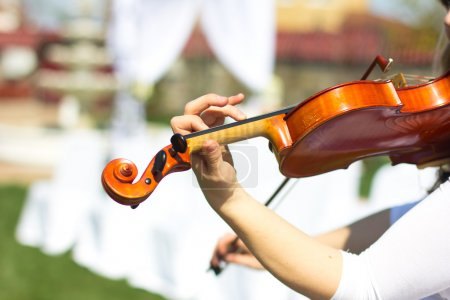 Photo for Girl playing on the violin outdoors. Musician for the wedding.Violin under the open sky - Royalty Free Image