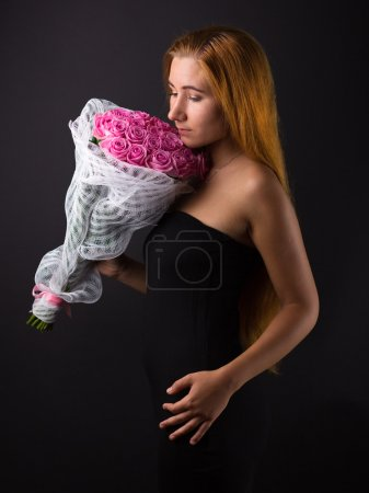 Beautiful girl with long hair with a large bouquet of roses. Long-haired girl with flowers. Gift girlfriend. Shiny hair on a black background
