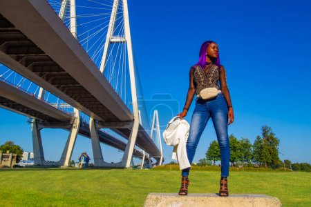 African-American woman against blue sky and a bridge. Dark-skinned model posing in the fresh air. African-American girl stands next to a cable-stayed bridge in Petersburg. Dark-skinned girl in Russia.