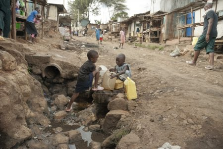 Photo pour Boys take a water for drinking on a street of Kibera, Nairobi, Kenya. Kibera is the biggest slum in Africa now. - image libre de droit