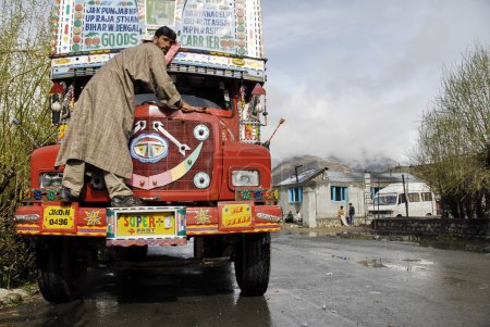 Indian driver washes his truck on a Srinagar - Leh road, India.