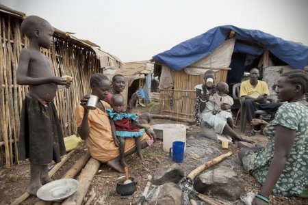 People have breakfast in front of their huts in displaced persons camp, Juba, South Sudan.