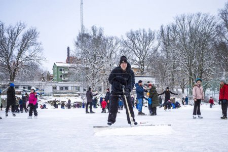 Photo for Stockholm, Sweden Ice skaters on a weekend in Aspudden park not wearing masks and a man plowing snow from the ice. - Royalty Free Image