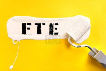 Photo pour Concept d'entreprise et de finance. Sur fond jaune, la surface est peinte en blanc avec un pinceau, sur lequel il est écrit FTE - image libre de droit