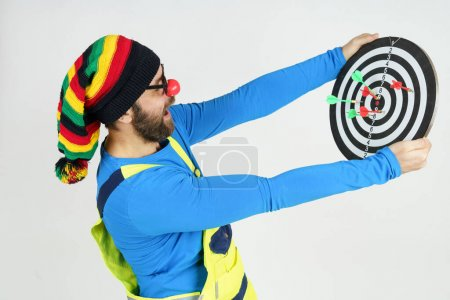 Photo for Celebration and communication concept. The clown holds a target in his hands, looks at the result of dart shooting. Isolated on white - Royalty Free Image