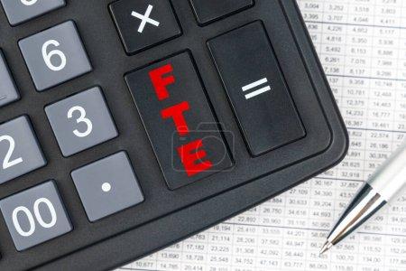 Photo pour Affaires et finances. Sur la table se trouve un rapport, un stylo et une calculatrice, sur la grande clé de laquelle est écrit - ETP - image libre de droit