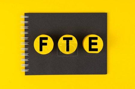 Photo pour Concept d'entreprise et de finance. Sur un fond jaune se trouve un carnet noir, cercles jaunes en bois avec l'inscription - ETP - image libre de droit