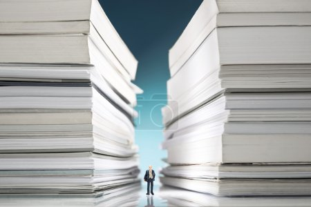 Photo pour Homme d'affaires miniature perdu dans une énorme pile de documents - image libre de droit