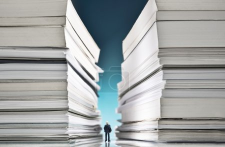 Photo for Miniature businessman lost into a huge pile of paperwork - Royalty Free Image