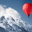 Colorful hot-air balloon flying over snowcapped mo...