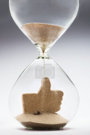 Photo for Like icon made out of falling sand inside hourglass - Royalty Free Image