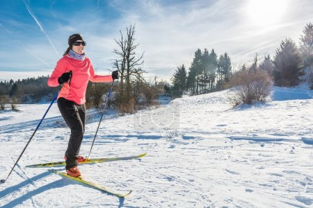 Woman cross country skiing on a yellow skis...