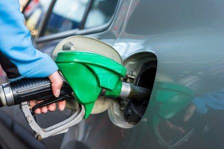 Punping gas at gas station.