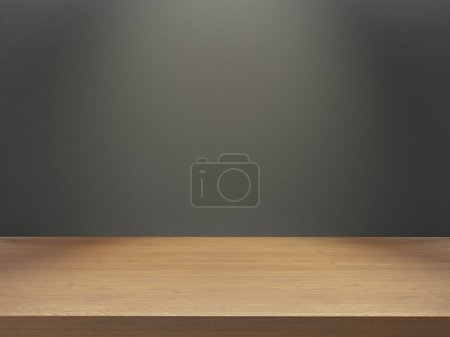 wooden desk with gray wall under light effect