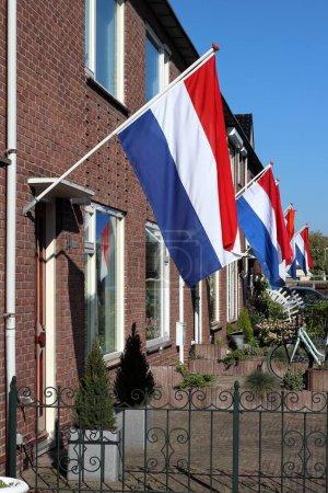 Photo pour Maisons de rue néerlandaises régulières avec drapeau national agitant et banderole orange. Koningsdag Kingsday et Bevrijdingsdag Liberation Day, Pays-Bas. - image libre de droit
