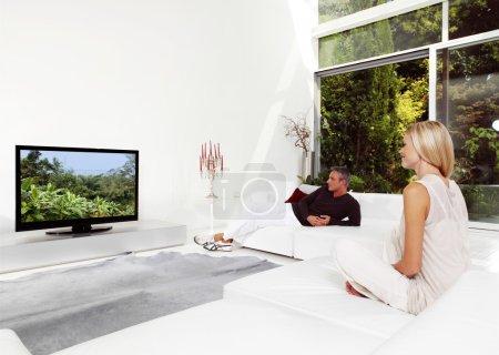 Photo pour Beau couple assis sur canapé à regarder la télévision - image libre de droit