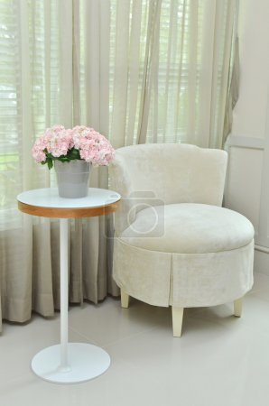 Interior design of modern room with chair, table and bouquet flower