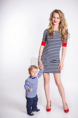 Mother with her son standing over the white background, blond, smiling, striped clothes, the family sailor