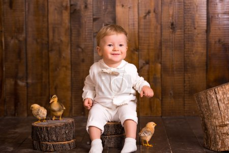 baby blond boy in a white suit white socks sitting on a wooden chair on a wooden background. next to a small duckling
