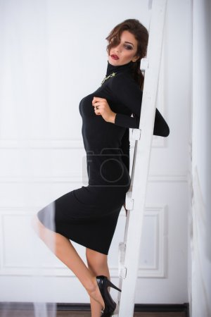 Young brunette woman in a black white dress on a white background, beautiful, tall, red lipstick, high heels, looking forward, looking down, beautiful eyes, bright makeup, smokey eyes