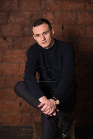 wealthy man, dark background, short-haired man, businessma, a man in a dark  sweater, blazer, looking directly into the camera, stern look, business, brick wall, dark background, red brick, bright smile,