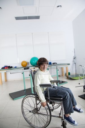 Photo pour Verticale d'un garçon dans le fauteuil roulant sur la réadaptation - image libre de droit