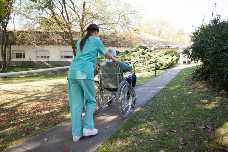 Nurse carrying a patient in a wheelchair in the park