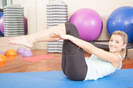 Photo pour Femme étirement dans le yoga sur tapis d'exercice - image libre de droit