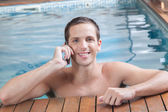 man talking on cellphone in the pool