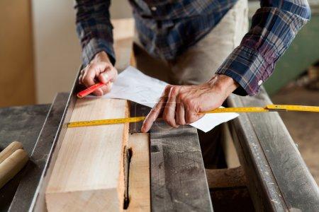 Carpenter measuring a plank
