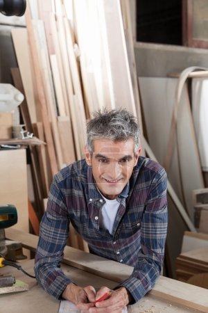 Smiling carpenter in his workshop