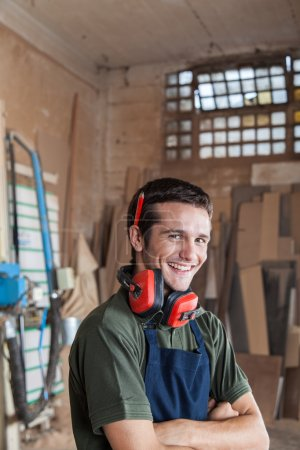 Carpenter smiling with protectors hearing