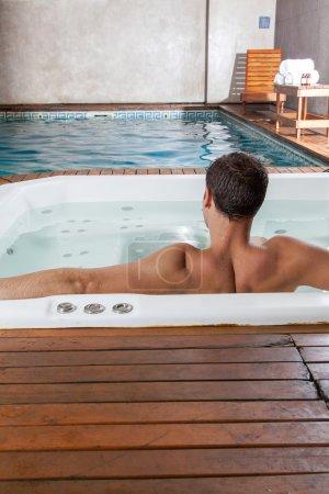 Photo pour Vue arrière du jeune homme à l'intérieur d'un bain à remous - image libre de droit