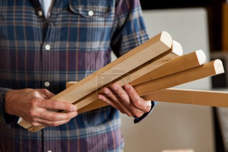 carpenter holding pieces of wood