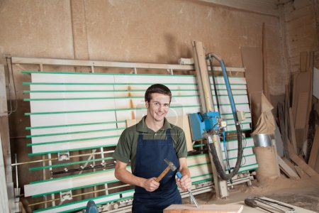Smiling carpenter working with a chisel