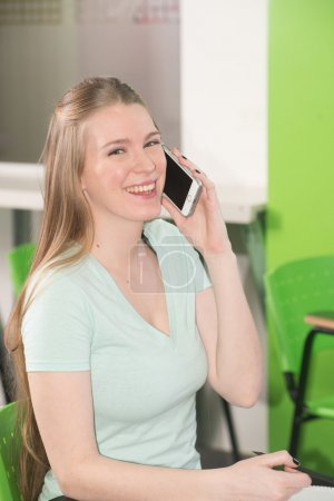girl talking on phone in classroom