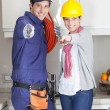 Happy pair of plumbers with tools in the kitchen...